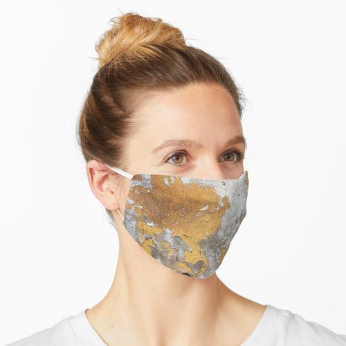 Metallfolie-Goldzauber auf grauer Betonmauer Maske